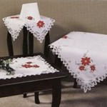 Elegant Christmas tablecloth with applique red poinsettias and Battenburg lace fully edged. Premium quality pure white cotton. Available in 7 sizes .