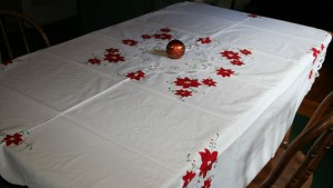 Appliqué Red Poinsettia with Battenburg Lace on pure white cotton sets a cheerful tone to a festive holiday celebration.
