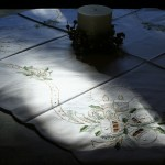 Green & Golden: Beautifully embroidered Candle Light Bells & Holly with gold thread with cutwork details. Pure white cotton for this holiday season. Table topper & Doily & runners available at a budget wise economy.