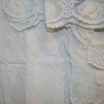 Hand knotted Modano Tuscan Lace rose motif embellished with Embroidered Roses Cushion Cover in Pristine White Cotton.