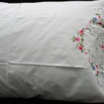 Hand Cross-Stitched Embroidery with intricately Hand Crocheted Lace edge all around the entire front and back of the pillow cases. Multi Colours on White. Queen size only.