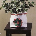 Applique Holly Wreath Gift Bag as indoor plant holder.