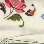 Close up of tent stitched peony with tent stitched hemmed border.