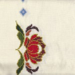 Needlework Peony on Pale Yellow cotton aida cloth close up view.